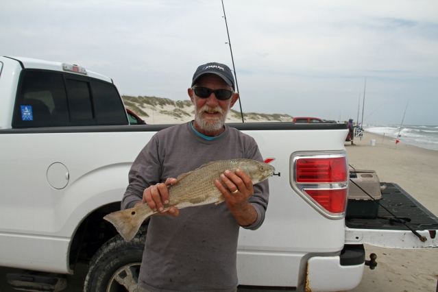 Bob Toth of Ocracoke holds a puppy drum he caught. Photo by P. Vankevich