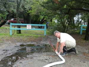 Andrew Havenhand, an Ocrafolk Festival volunteer, holds hoses together while John Brock pumps water from a large puddle on the Books To Be Red grounds. Photo: C. Leinbach
