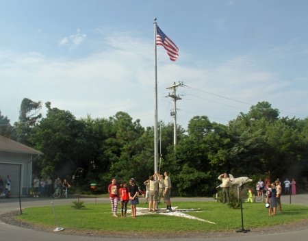 Boy Scout Troop 290 raise the flag as Mariah Temple, Alyssa Bryann and Maren Donlon sing the National Anthem. Photo by P. Vankevich