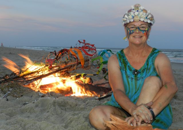 """Kitty Mitchell in her crown of sea shells at her """"Burning Woman"""" beach bonfire."""