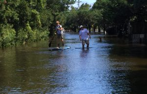Wyatt Spencer with his dad Nathan, makes the most of storm surge waters on Sunset Drive. Photo: C. Leinbach