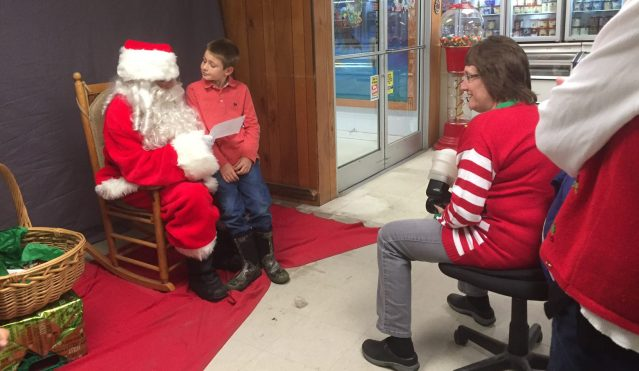 Santa Claus visited the Variety Store on Friday. Trudy Austin, right, takes complimentary photos of the kids and Santa.