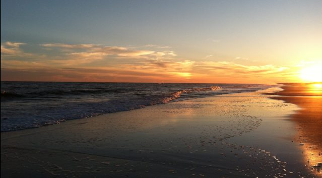 A sun dog (the small rainbow effect to the left of the setting sun in this shot) is a weather phenomenon that can be seen on Ocracoke. Photo: C. Leinbach